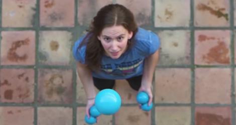 Une fille jongle avec 5 balles