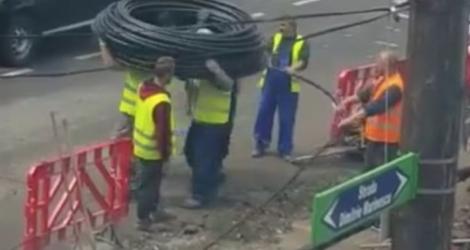 Des ouvriers déroulent un cable à plusieurs